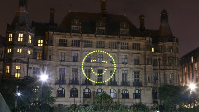 Happy face projected onto wall in peace gardens