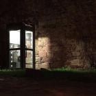 A lit up phonebox in dark surroundings