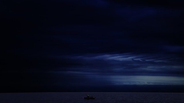 A small boat on a dark, calm ocean at night.