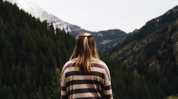 lady stood in front of mountains as if looking towards a journey