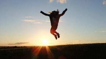 Person jumping in the air in front of sunrise