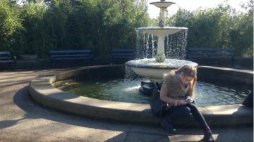 girl sitting by fountain