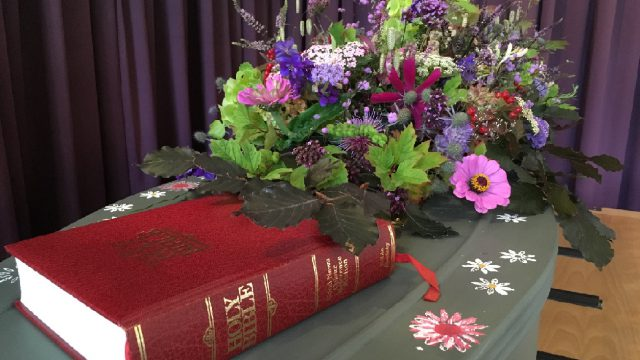 coffin with flowers and bible on top