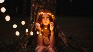 These well worn toys: girl sitting with a crown of fairy lights