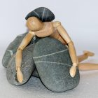 prone wooden figure lying on stones with a stone on its back