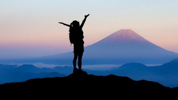 silhouette of a woman stood on top of a mountain with arms outstretched