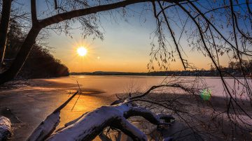 low sun shining over a frozen lake