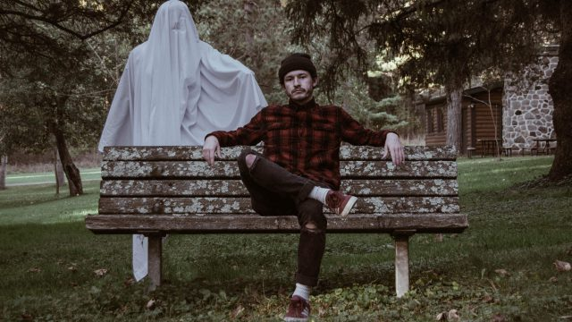 ghost stood behind a man on a bench