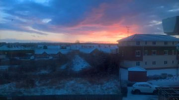 sun rising over snowy houses