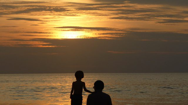 father and son looking at sunset
