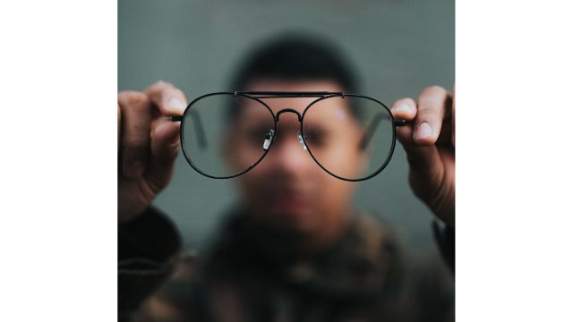 Out of focus Black man holding glasses
