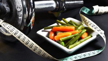 Small portion of food with a measuring tape and exercise weights